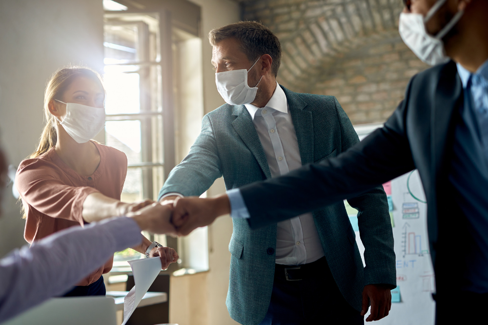 Employees wearing masks in the workplace to prevent the spread of covid-19 and reduce coronavirus business liability lawsuits