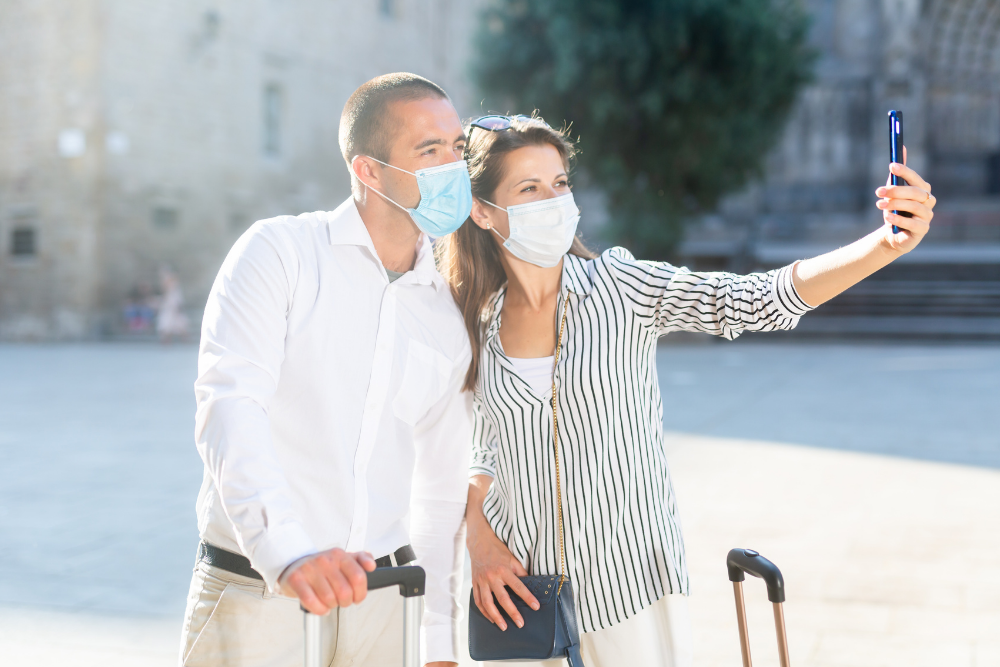 Man and woman wearing masks taking a selfie while on employee vacation time during the covid-19 pandemic