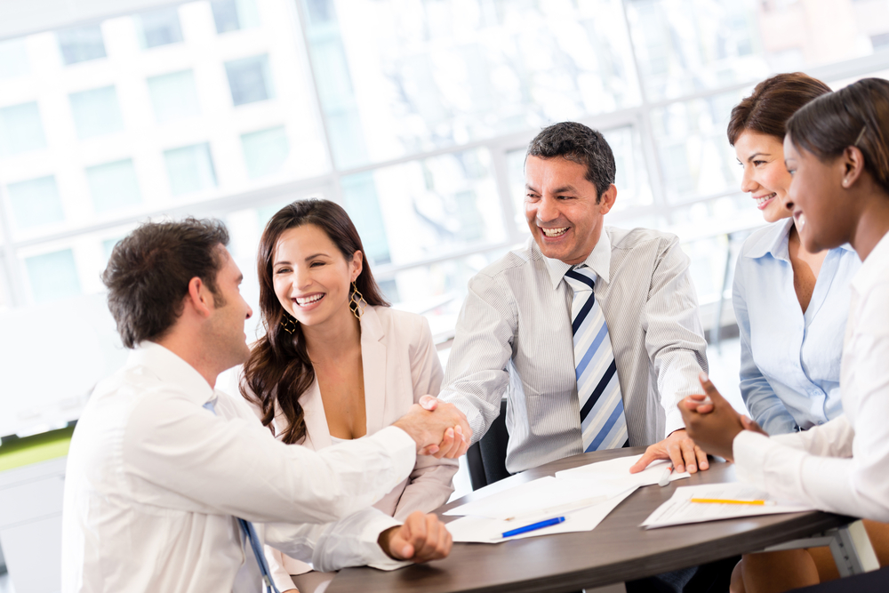 Business handshake in the middle of a meeting at the office