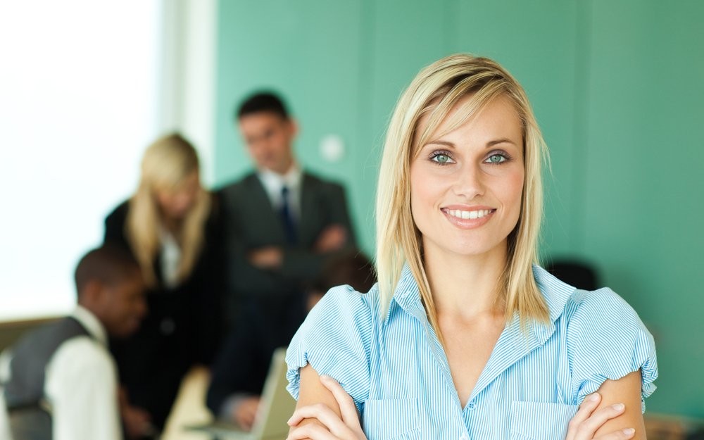 Businesswoman in front of people working in a green office