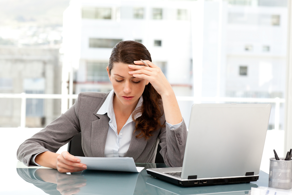 Pensive businesswoman looking at a paper while working on her laptop at her desk