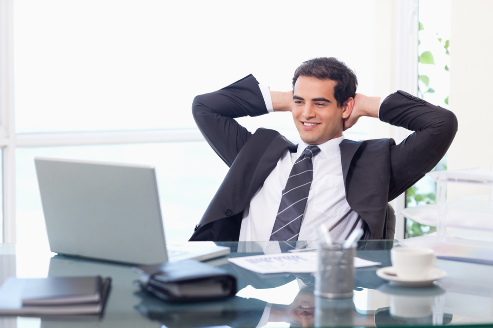 Relaxed businessman working with a laptop in his office
