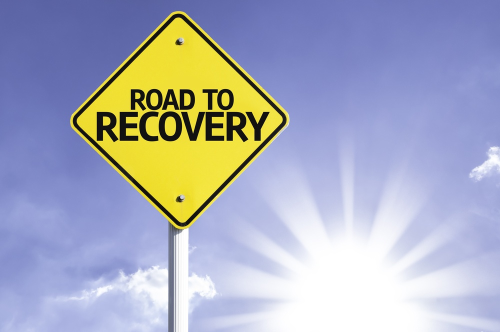 Road To Recovery road sign with sun background