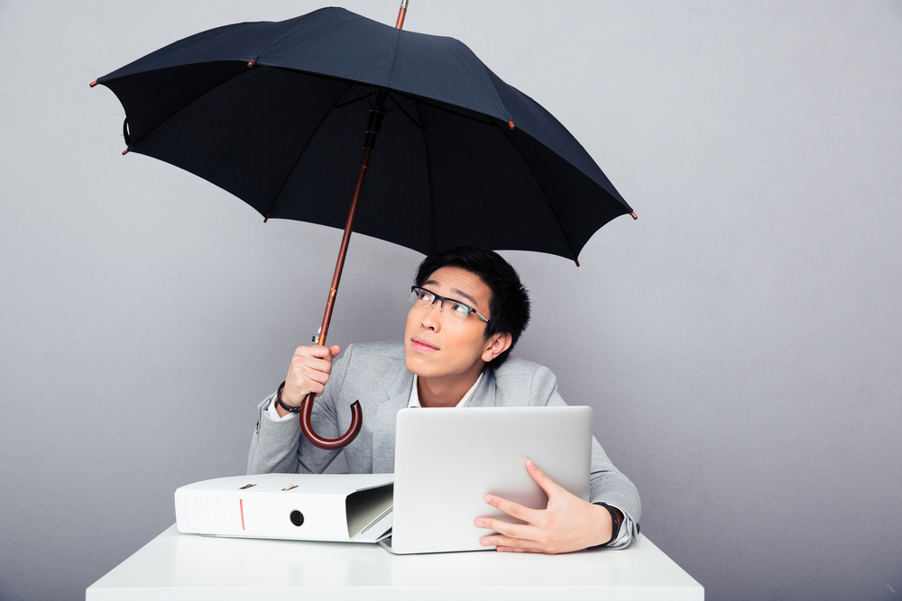 Young asian businessman sitting at the table with laptop and holding umbrella over gray background. Looking up