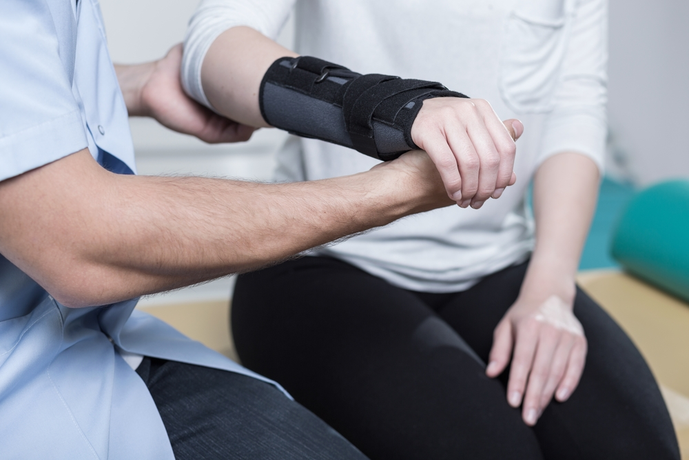 Woman using wrist immobiliser after hands injury