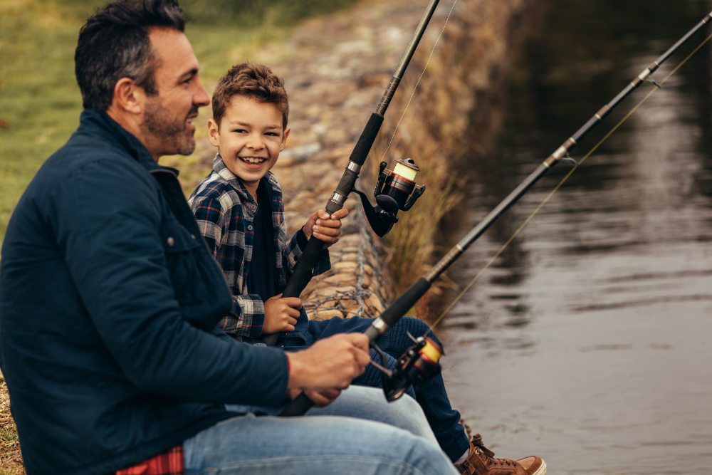father and son fishing while man enjoys the health benefits of taking time off work
