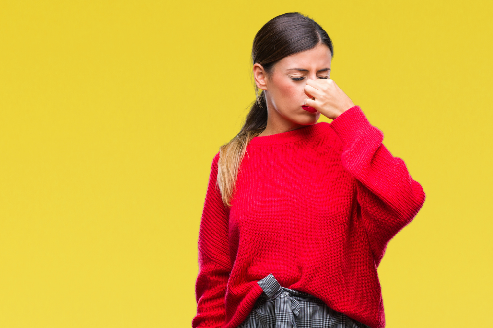 woman pinching nose because coworker smells bad