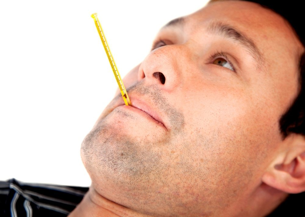 Man with a fever and a thermometer on his mouth isolated
