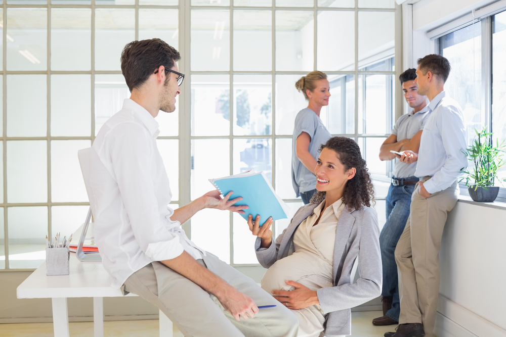 Pregnant businesswoman talking with colleague sitting at desk in the office